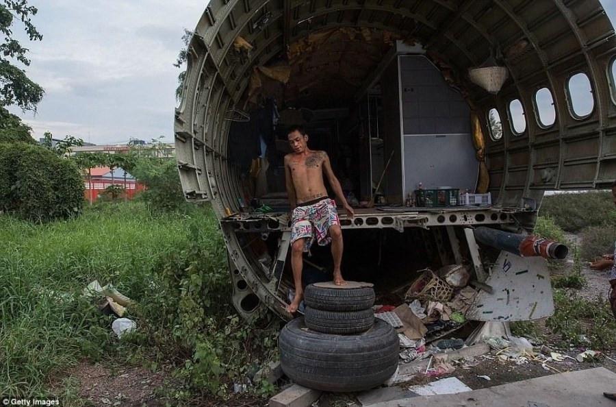 据每日邮报报道,在曼谷郊区的一处飞机废弃场,居住着当地的一些穷困人家。这些无家可归的人们常年居住在被遗弃的机舱里,靠着收捡破烂营生。从几年前起就陆续有废弃的飞机被堆放到这里,其中还有如波音747类型的大型客机。无人看管和处置的飞机坟场显得脏乱破败,与周边高耸的建筑日益形成鲜明的对比。